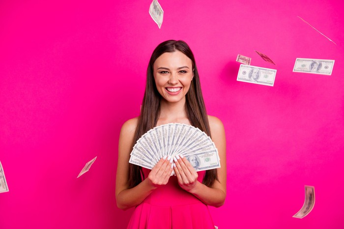 Smiling young woman fanning a large number of $100 bills.