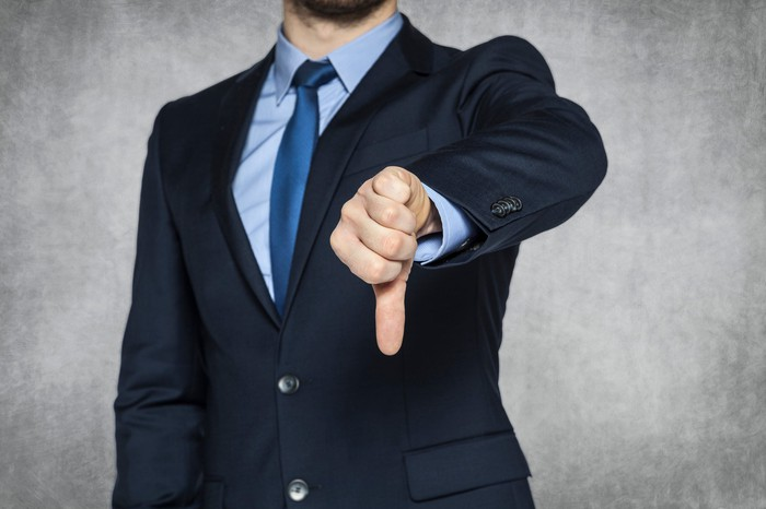 A business person in a suit giving the thumbs-down sign.