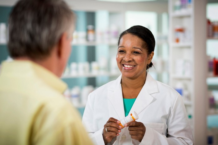 A smiling pharmacist speaking with a customer and holding a prescription bottle.
