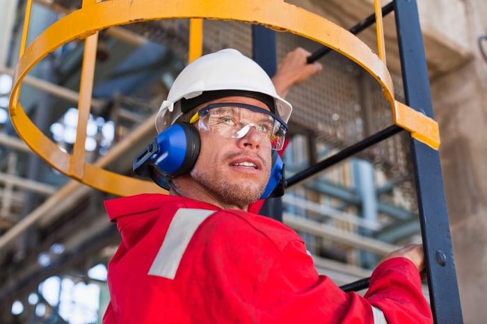 A worker climbs a ladder at an oil refinery.