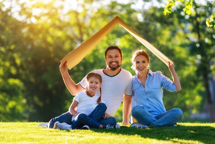 Family holding a cardboard box as a symbol of a house.