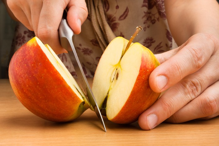 An apple getting sliced in half on a table.