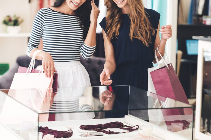 Two women look at lingerie inside a glass case in a store.