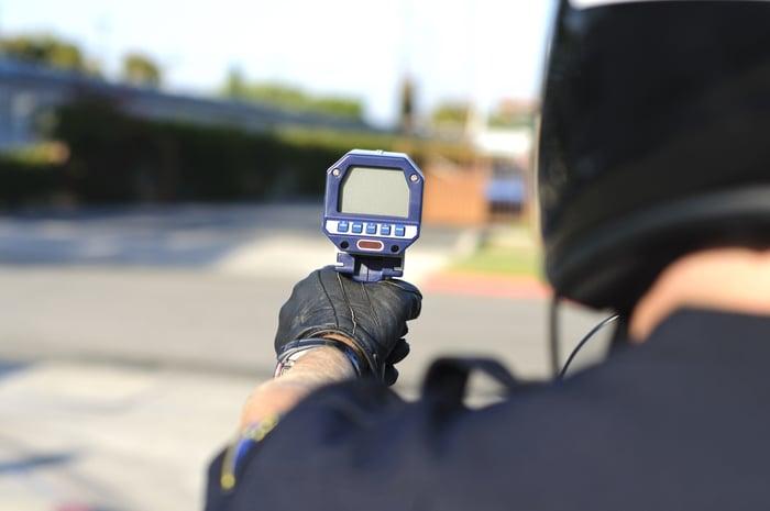 Officer pointing a radar gun at a passing vehicle.