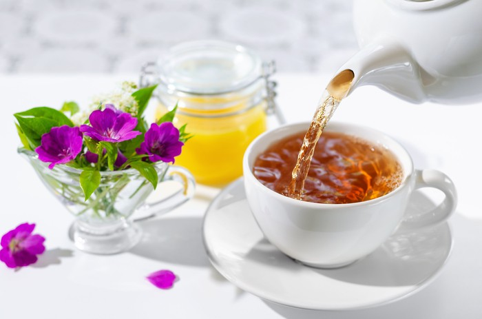 A cup of tea being poured from a teapot next to some flowers in a crystal teacup