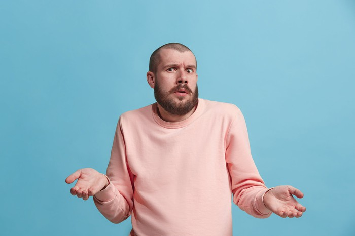 A person in a pink sweatshirt with a confused expression.