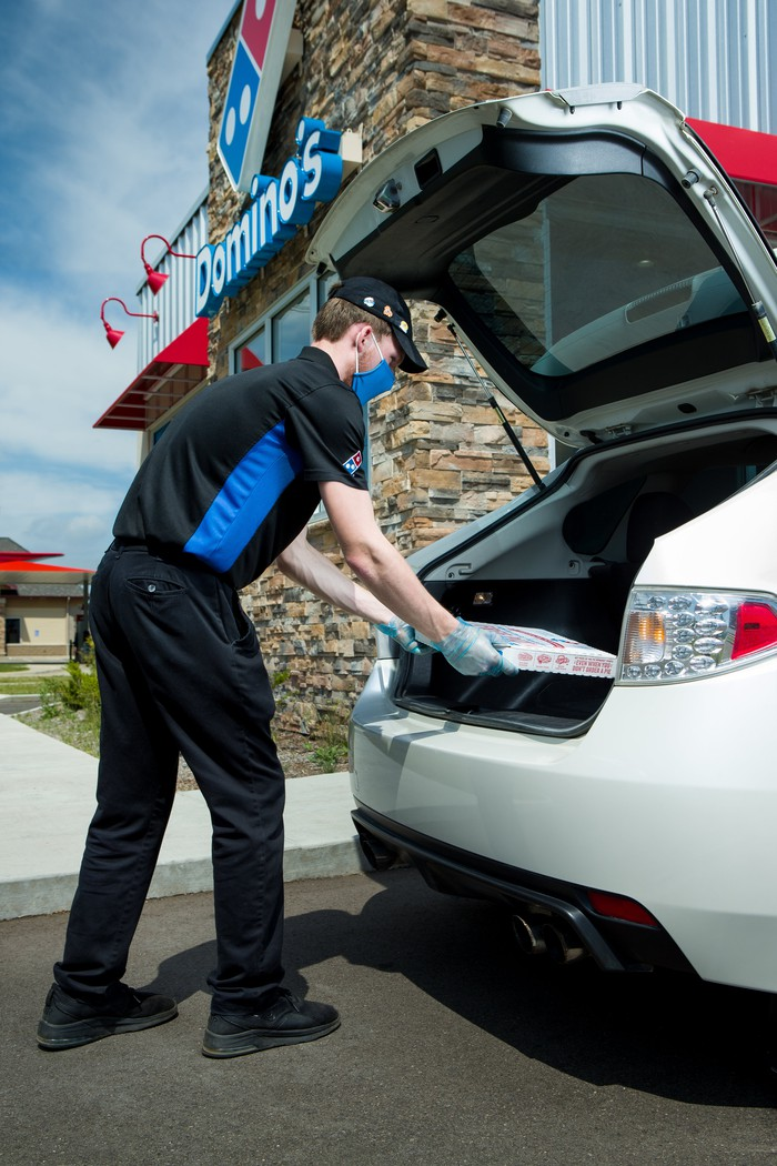 Domino's worker places pizzas in a customer's car