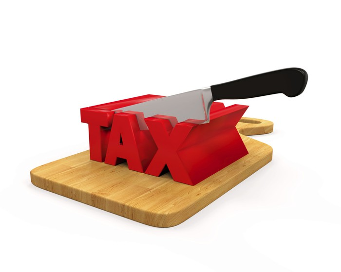We see a knife cutting a 3-d representation of the word tax.