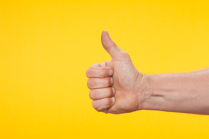 Close-up of a hand making a thumbs-up gesture.