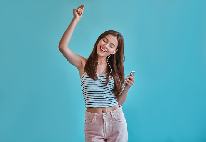 A young woman smiling while dancing to music on headphones.