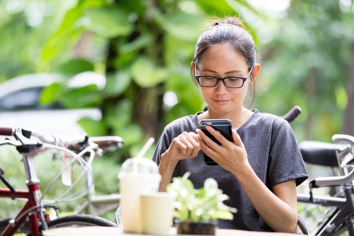 Young woman using a smartphone while seated at a table.