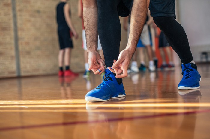 Man tying shoelaces of his basketball shoes on court.