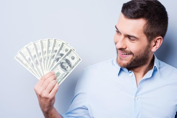 Smiling man holding handful of $100 bills