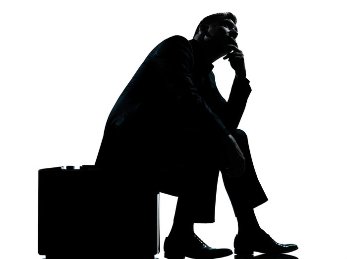 A businessman sits on his briefcase in deep thought.