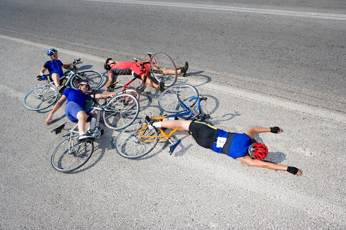 Four bicyclists who have crashed, lying in the road.