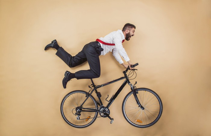 Man in office clothes in action over a bike, possibly about to fall.