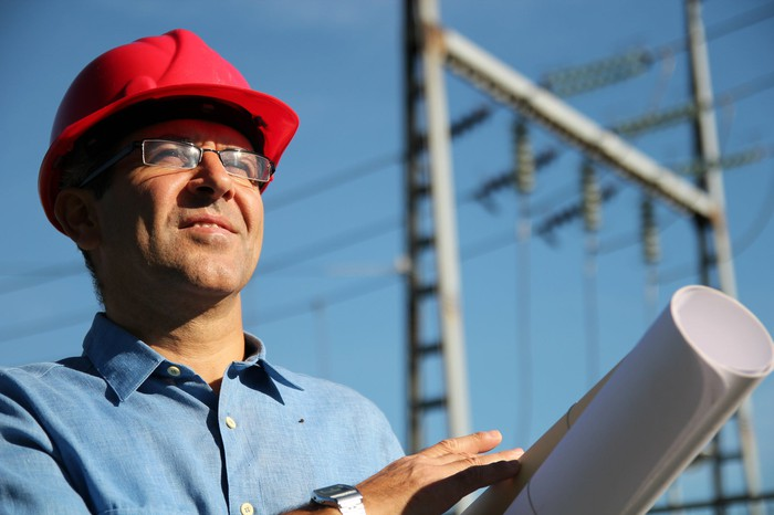 A man wearing a hard hat and carrying blueprints with high-voltage power lines behind him
