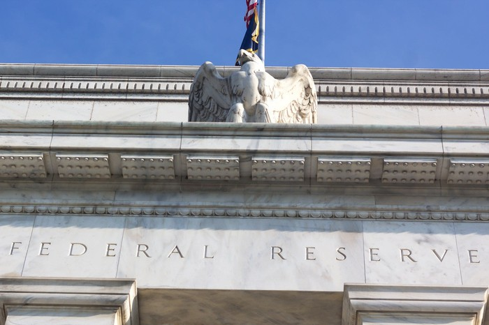Top arch of Federal Reserve building, with eagle, flag, and engraved marble shown.