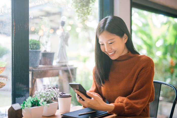 Woman sitting at a small table with some small potted plants, a takeout beverage, and a notebook on it, while smiling at her smartphone in her hands