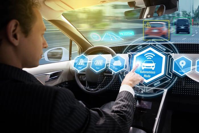 A driver pressing a self-driving auto button in car