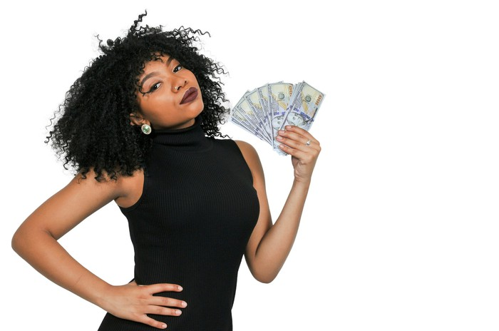 A young woman holds a fan of $100 bills.