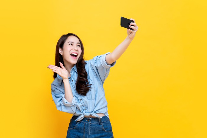 Woman waving to smartphone