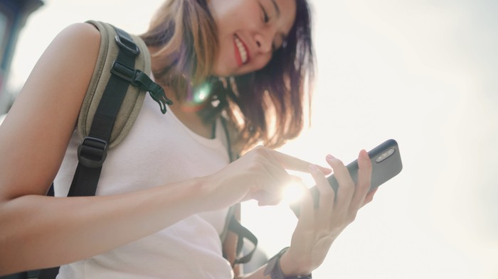 A young person carrying a backpack smiles as they use their cellphone.