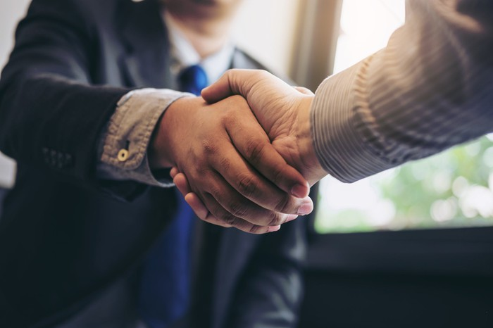 Two business people shaking hands during a meeting.