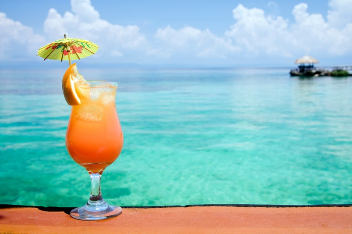 A tropical drink with an umbrella and a view of the ocean.