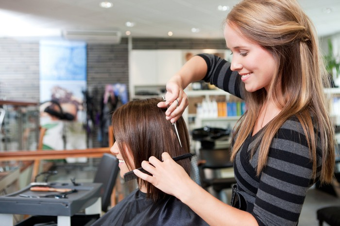 A woman cuts another woman's hair in a salon setting