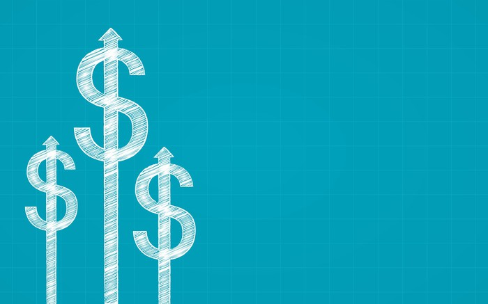 Illustration of three dollar signs in white chalk on a blue background.