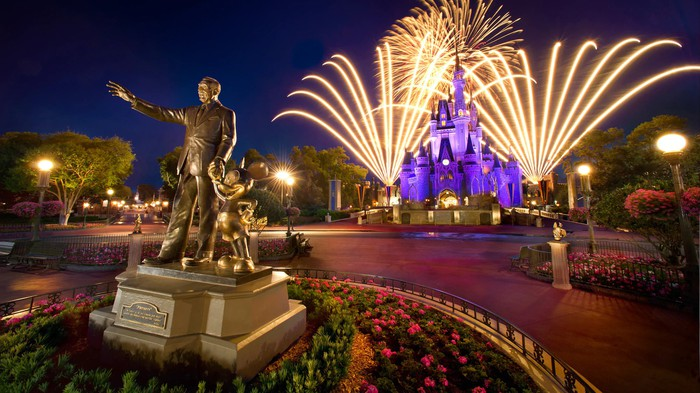 Fireworks at night over the Cinderella Castle and a bronze statue of Mickey and Walt Disney.