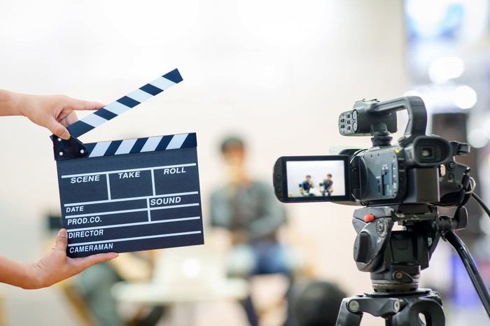 Photo of a movie camera and two hands holding a clapper in front of two blurred actors.