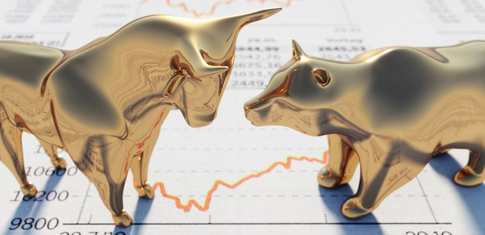 Bull and bear figurines standing on a newspaper page with stock quotes and charts on it.