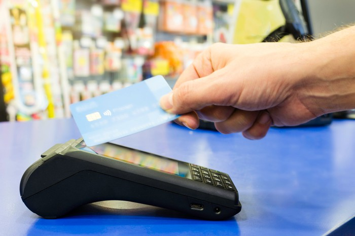 Customer waving a payment card at a reader in a non-contact transaction.