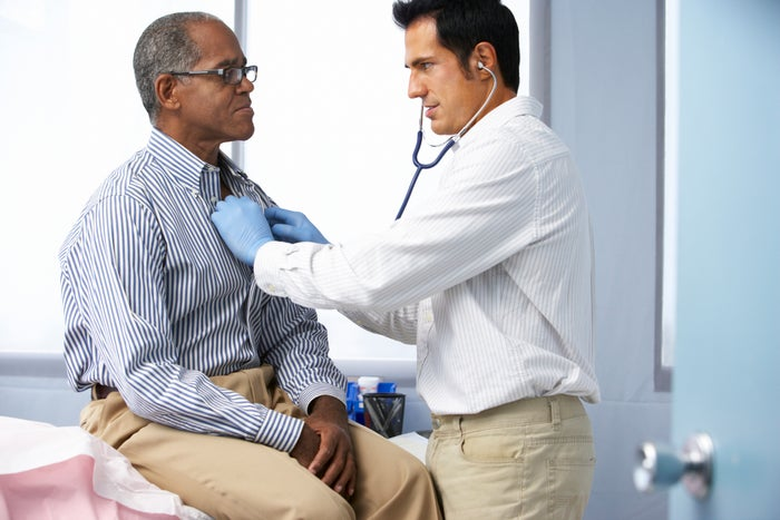 A doctor listens to an older man's chest with a stethoscope.