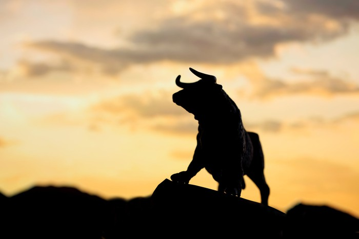 Silhouette of a bull on top of a mountain.
