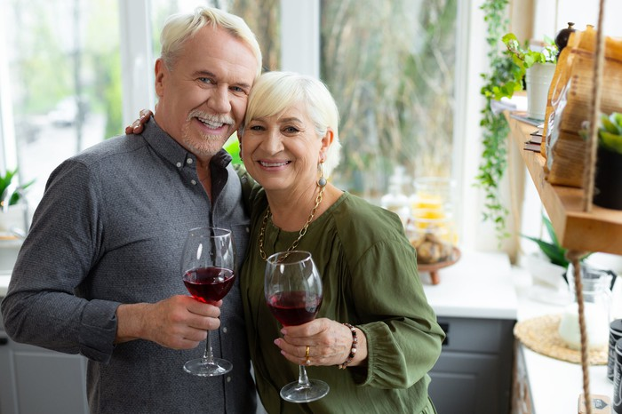 Older man and woman holding wine glasses