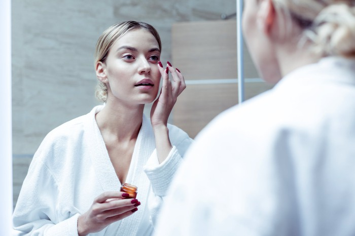 A woman in a robe applying an eye cream while looking in a mirror
