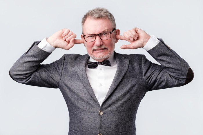 An old man in a grey suit plugs his ears with his index fingers.