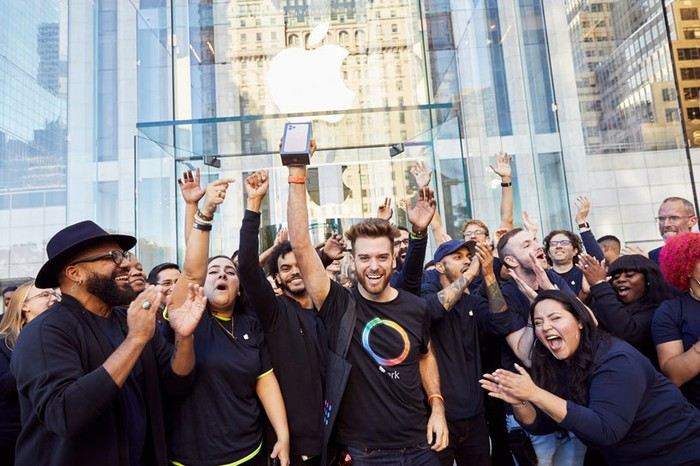 Apple team members cheering for a customer holding a new iPhone in front of an Apple store.
