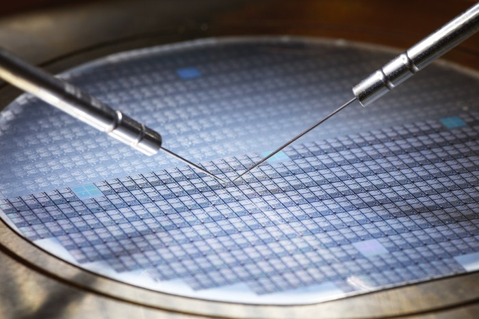 Two metal prongs etch something onto a round silicon wafer.
