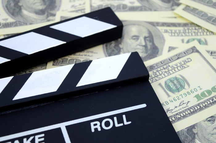 Movie production take and roll chalkboard atop a pile of $100 bills