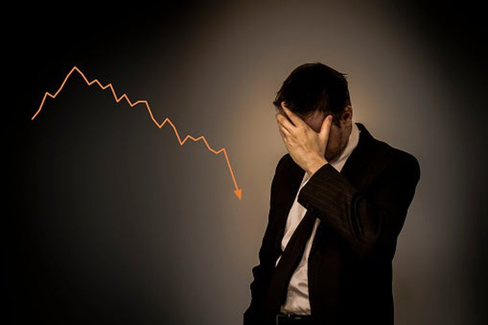 A guy in a suit with his head in his hands as a stock chart heads lower behind him.