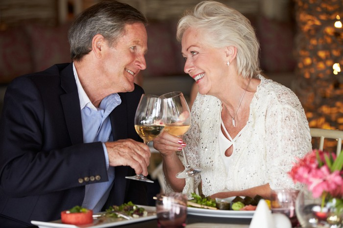Nicely dressed older man and woman smiling at each other, clinking wine glasses