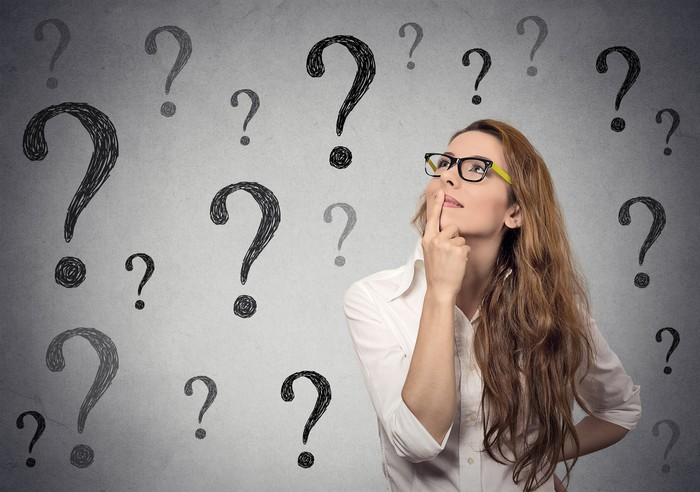 Woman wearing glasses looking up at many question marks.