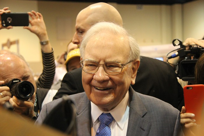 Warren Buffett smiles while surrounded by photographers.