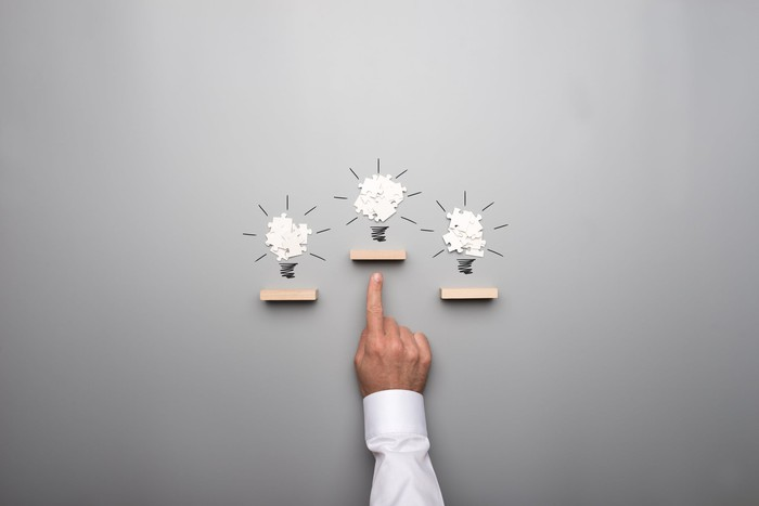A person pointing at a pile of puzzle pieces in the shape of a lightbulb between two other such piles.