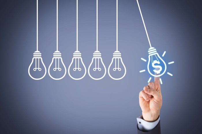 Finger pointing to drawing of a pendulum light bulb with a dollar sign in it next to a row of ordinary pendulum bulbs.