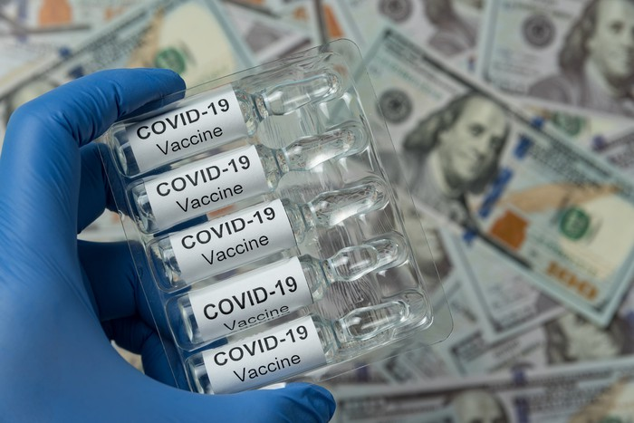 Gloved hand holding vials labeled COVID-19 vaccine over a pile of hundred-dollar bills